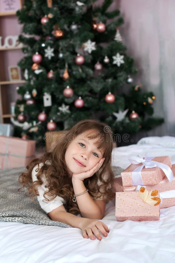 Merry Christmas and happy holidays! New Year 2020! A cute girl in pajamas opens gifts in her children`s room against the backgroun. D of the New Year tree. The stock image
