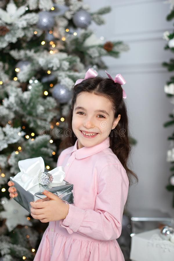 Merry Christmas and happy holidays! New Year 2020. Happy little girl with christmas present at home. kid holds gift box near Chris royalty free stock photos