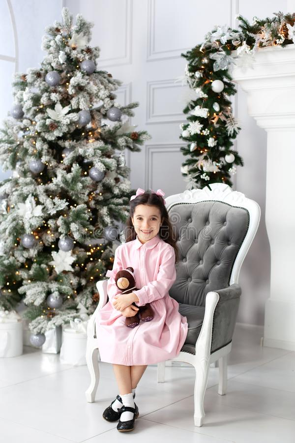 Merry Christmas and happy holidays! New Year 2020. Happy little girl in dress plays with teddy bear on an armchair in living room. royalty free stock photography