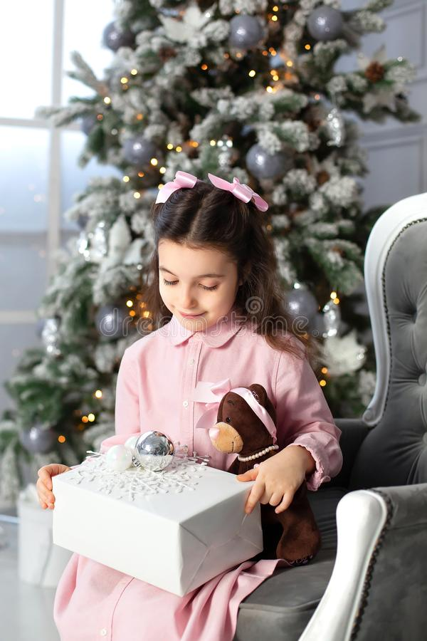 Merry Christmas, happy holidays. New Year. little girl with bows on her head and in dress opens gift in living room on Christmas E stock images