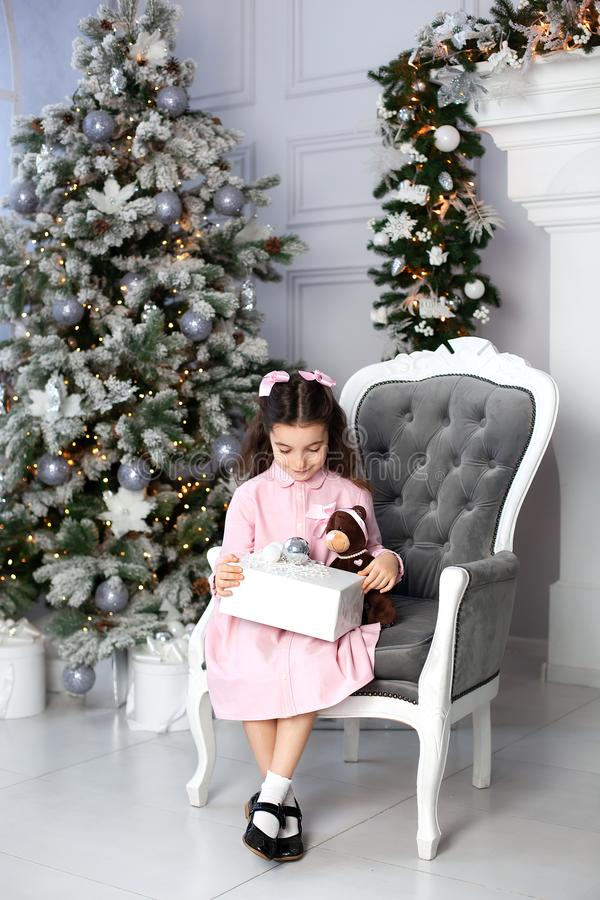 Merry Christmas, happy holidays. New Year 2020. little girl with bows on her head opens a gift in living room on Christmas Eve. ch royalty free stock image