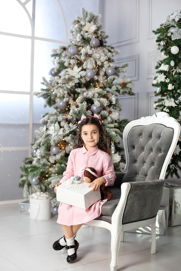 Merry Christmas, happy holidays. New Year 2020. little girl with bows on her head and in pink dress with gifts in living room on C stock photos