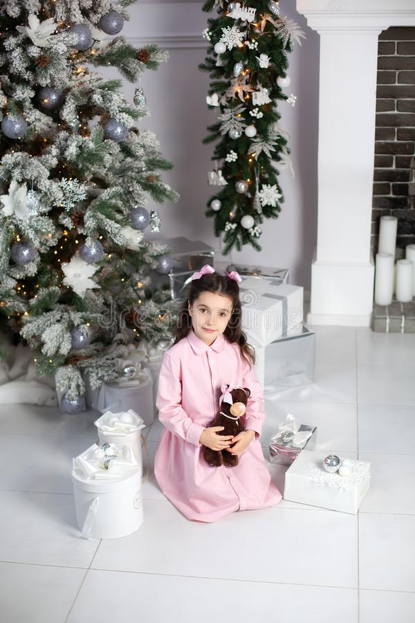 Merry Christmas, happy holidays. New Year 2020. little girl with bows on her head and in pink dress with gifts in living room on C royalty free stock photography