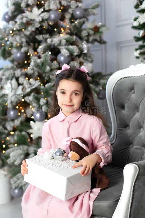 Merry Christmas, happy holidays. New Year 2020. little girl with bows on her head and in pink dress with gifts in living room on C stock photography