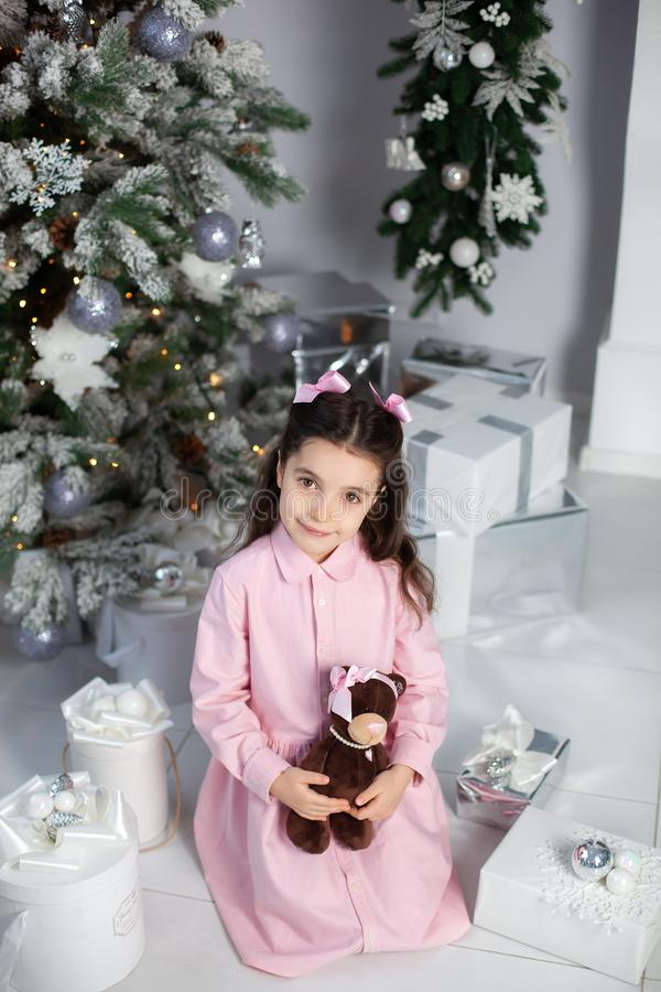 Merry Christmas, happy holidays! New Year 2020. Happy little girl with Christmas gifts at home. child holds teddy bear near Christ royalty free stock image