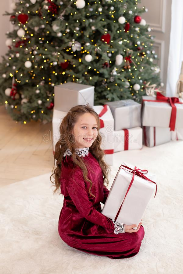 Merry Christmas and happy holidays. New Year 2020. A little girl opens a magical Christmas present in living room. child holds a C royalty free stock image