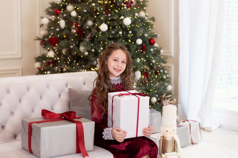 Merry Christmas and happy holidays! New Year 2020. Happy little girl with christmas present at home. kid holds gift box near Chris royalty free stock images