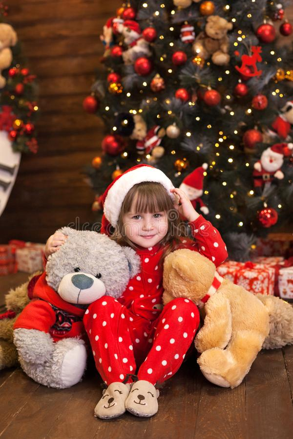 Merry Christmas, happy holidays. New Year 2020. Little girl in red pajamas sitting with gifts by the Christmas tree in the living. Room on Christmas Eve. A royalty free stock image