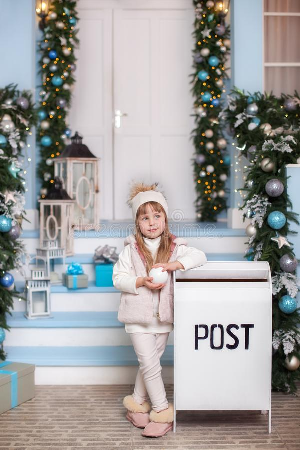 Merry Christmas, happy holidays! New Year. little girl stands near mailbox in yard of house in winter. girl sent letter to Santa C. Laus with list of Christmas stock photos