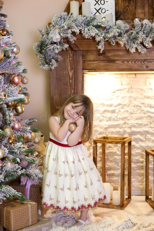 Merry Christmas and happy holidays! New Year 2020. Portrait of a cute little girl decorates a Christmas tree in the living room wi royalty free stock photo