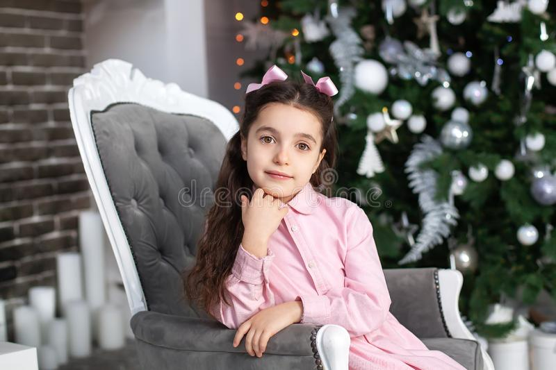 Merry Christmas, happy holidays! New Year 2020. Portrait of little girl with bows on head daydreaming for Christmas near Christmas stock photo