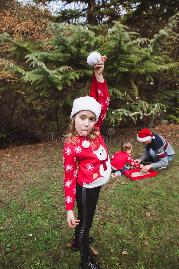 Merry Christmas and Happy Holidays. Pretty girl in red sweater and Christmas hat has fun, and her family decorates a Christmas tre stock images