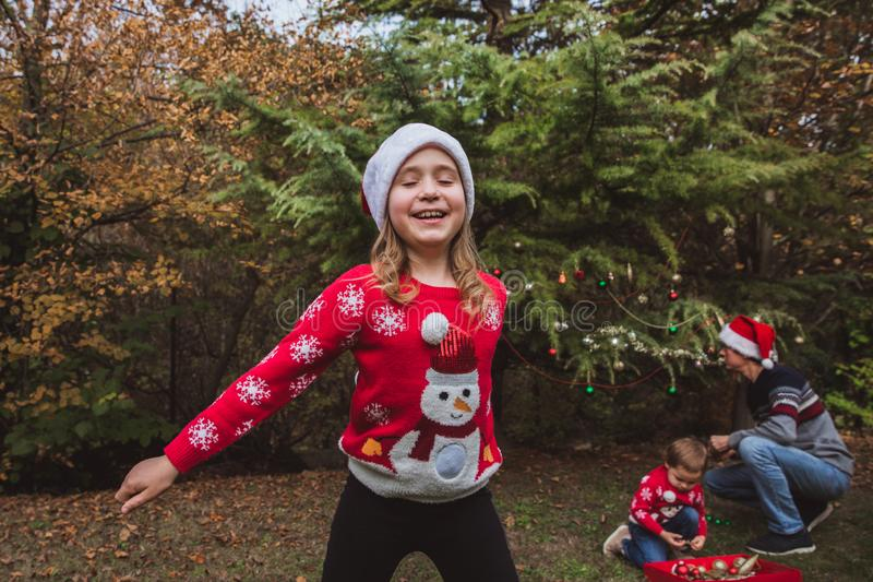 Merry Christmas and Happy Holidays. Pretty girl in red sweater and Christmas hat has fun, and her family decorates a Christmas tre. Pretty girl in red sweater royalty free stock image