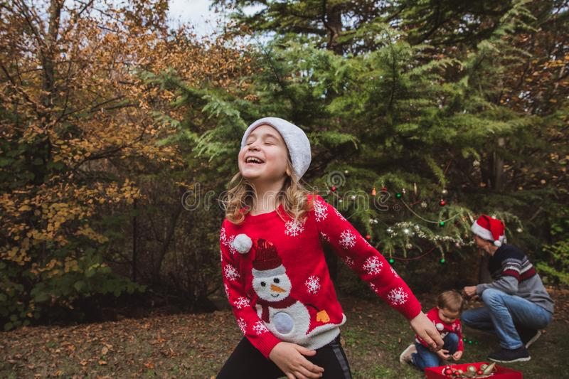 Merry Christmas and Happy Holidays. Pretty girl in red sweater and Christmas hat has fun, and her family decorates a Christmas tre. Pretty girl in red sweater royalty free stock photography