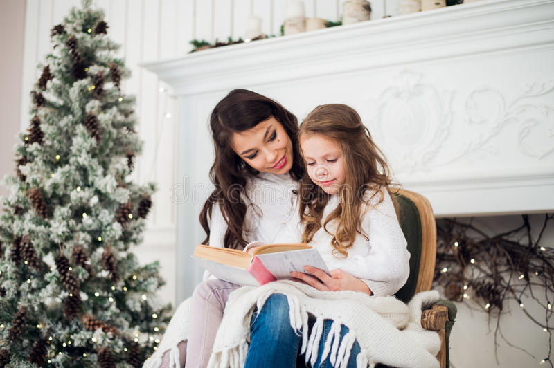 Merry Christmas and Happy Holidays, Pretty young mom reading a book to her cute daughter near tree indoors. royalty free stock photography
