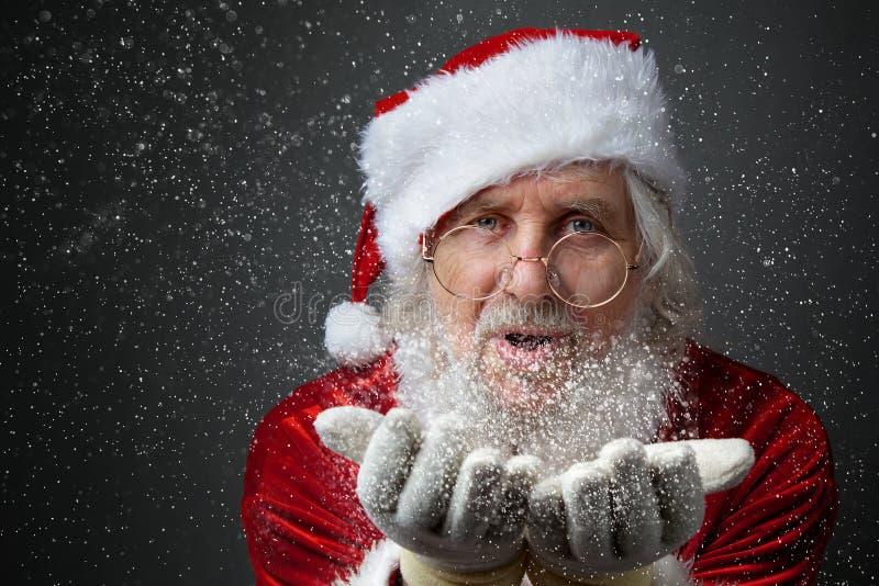 Santa Claus blows snow. royalty free stock photography