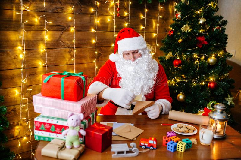 Merry Christmas and Happy Holidays. Santa Clause is preparing gifts for children for Xmas at desk at home. stock images