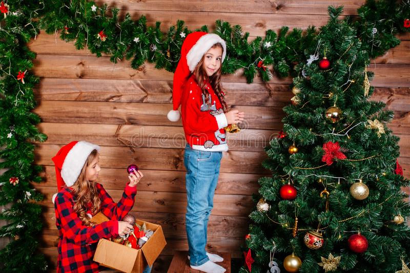 Two cute little child girls is decorating the Christmas tree indoors. Merry Christmas and Happy Holidays. Two cute little child girls is decorating the Christmas stock photos