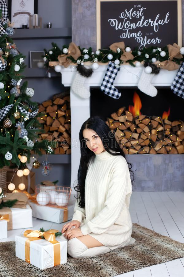 Merry Christmas, happy holidays! Woman in white sweater, warm and cozy evening in New Year interior design, a tree, gifts, a firep. Lace with socks, garlands stock photography