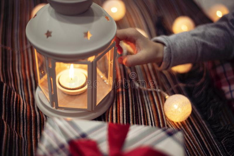 Merry Christmas and Happy Holidays!  Xmas winter holidays concept. Child girl hand holding a candlestick. Christmas decoration,. Festive lights stock photo