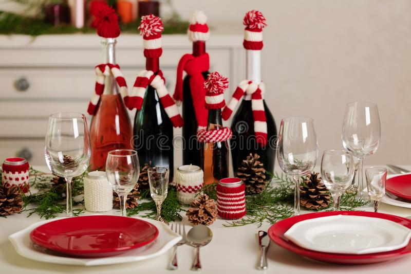 Merry Christmas and Happy New Year! Тable setting holiday knitted decor - Santa Claus knitted hats on the bottle with. Wine, candles in candlesticks in stock images