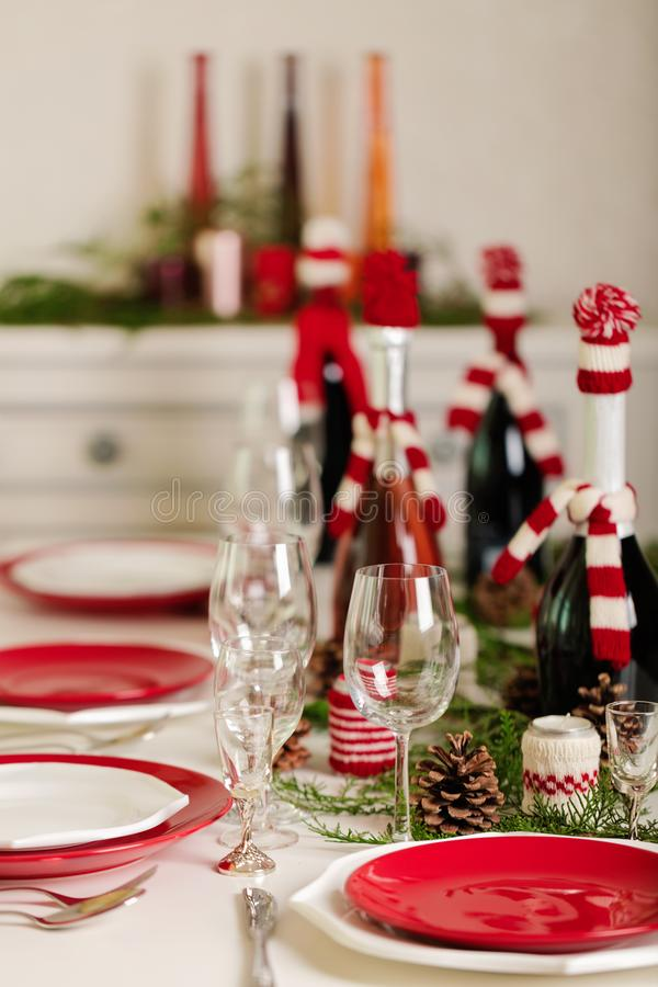 Merry Christmas and Happy New Year! Тable setting holiday knitted decor - Santa Claus knitted hats on the bottle with. Wine, candles in candlesticks in royalty free stock photo
