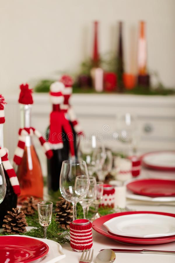 Merry Christmas and Happy New Year! Тable setting holiday knitted decor - Santa Claus knitted hats on the bottle with. Wine, candles in candlesticks in royalty free stock photos