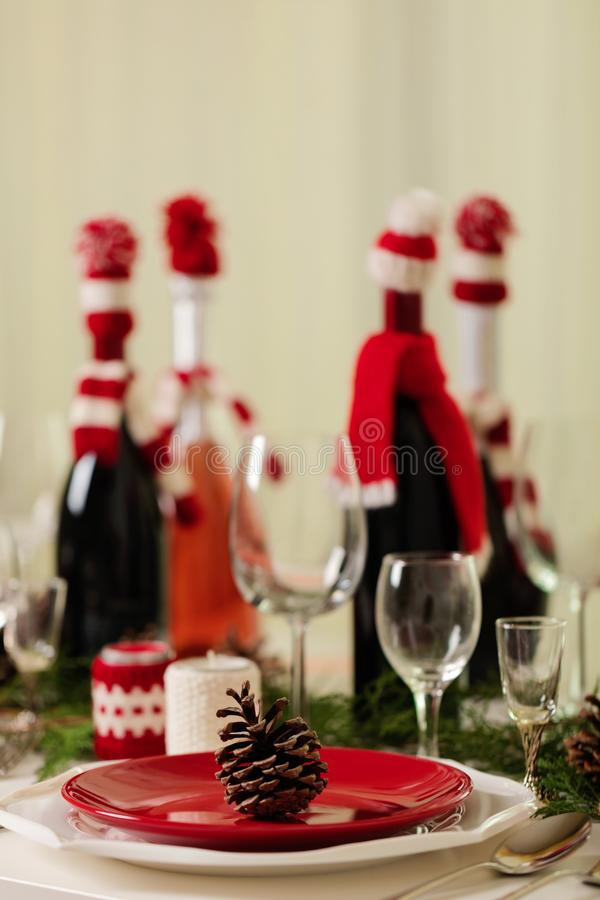 Merry Christmas and Happy New Year! Тable setting holiday knitted decor - Santa Claus knitted hats on the bottle with. Wine, candles in candlesticks in stock photography