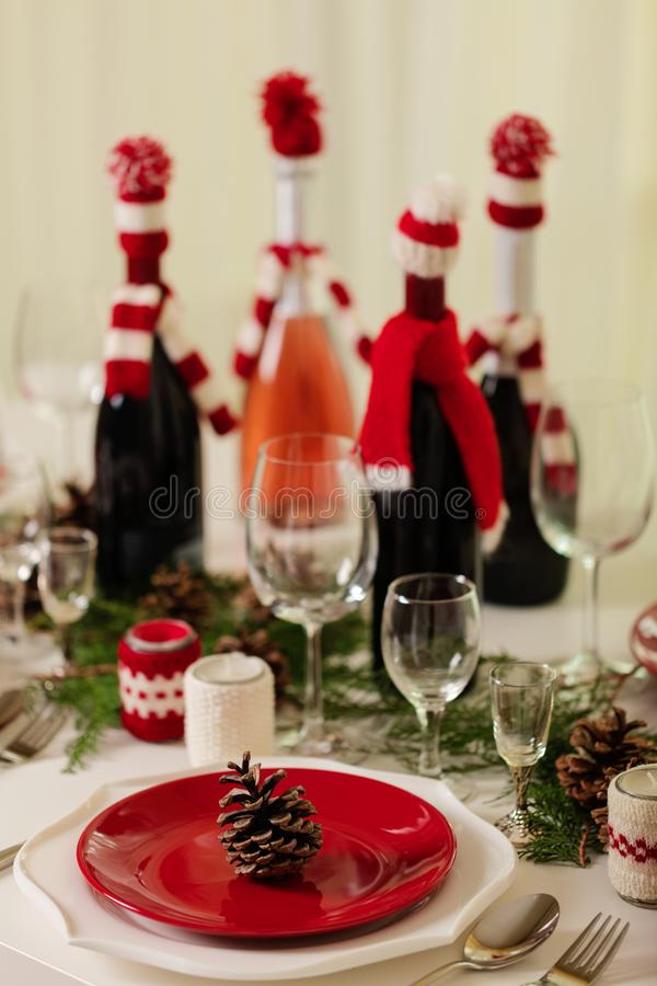 Merry Christmas and Happy New Year! Тable setting holiday knitted decor - Santa Claus knitted hats on the bottle with. Wine, candles in candlesticks in stock photo