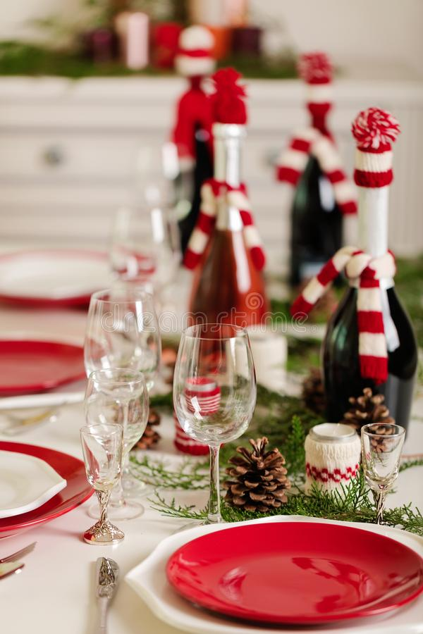 Merry Christmas and Happy New Year! Тable setting holiday knitted decor - Santa Claus knitted hats on the bottle with. Wine, candles in candlesticks in stock photos