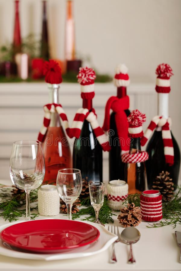 Merry Christmas and Happy New Year! Тable setting holiday knitted decor - Santa Claus knitted hats on the bottle with. Wine, candles in candlesticks in royalty free stock images