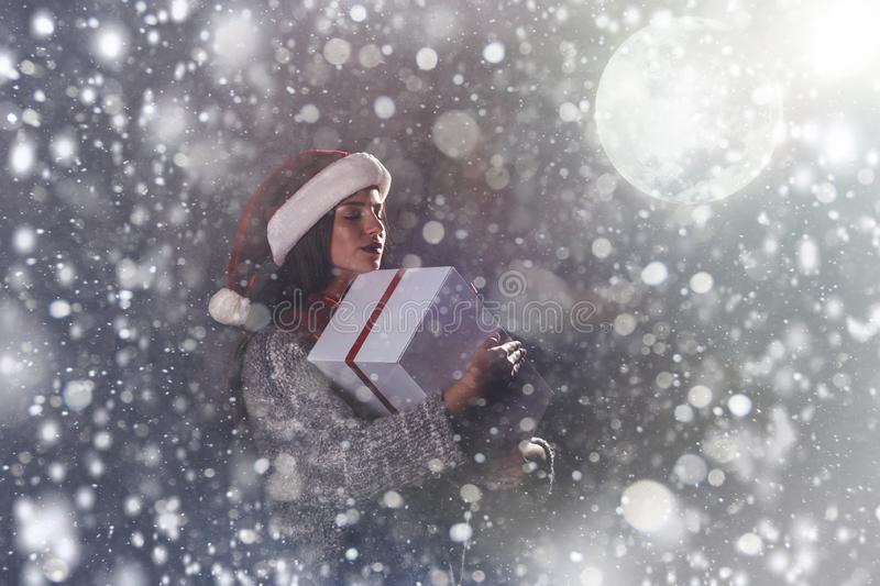 Merry Christmas and happy new year! Adorable female hold present in hands. Close portrait on gray background. Girl in santa hat. And sweater dreaming under stock image