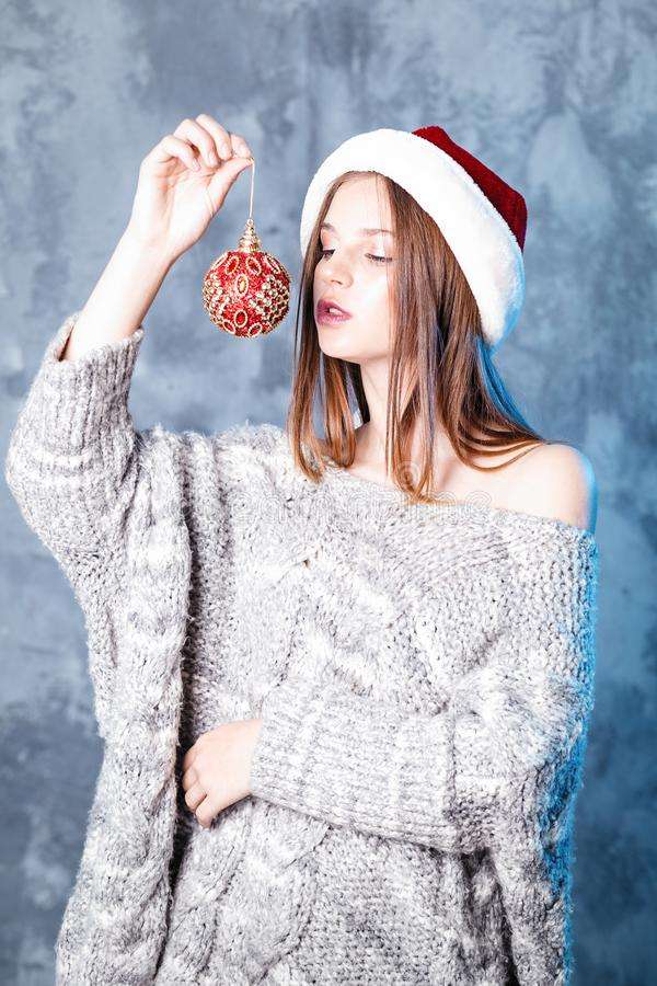 Merry Christmas and happy new year! Adorable girl with ball toy in hands looks very cheeky. Close portrait on gray background. Girl in santa hat and sweater royalty free stock photos