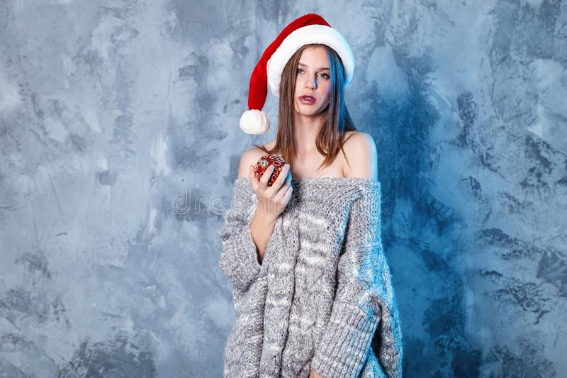 Merry Christmas and happy new year! Adorable girl with ball toy in hands looks very cheeky. Close portrait on gray background. Girl in santa hat and sweater stock photography