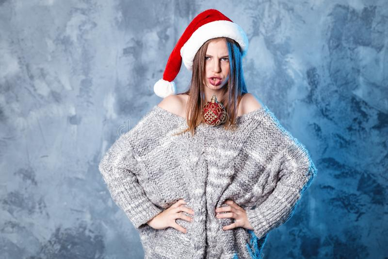 Merry Christmas and happy new year! Adorable girl with ball toy in mouth looks very cheeky. Close portrait on gray background. Girl in santa hat and sweater stock photography