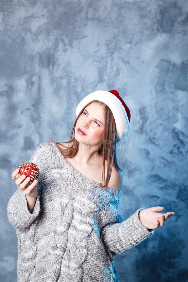 Merry Christmas and happy new year! Adorable girl with ball toy in mouth looks very puzzled. Close portrait on gray background. Girl in santa hat and sweater royalty free stock photography