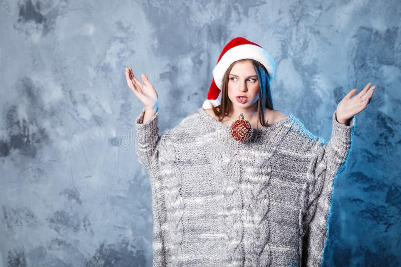 Merry Christmas and happy new year! Adorable girl with ball toy in mouth looks very puzzled. Close portrait on gray background. Girl in santa hat and sweater royalty free stock image