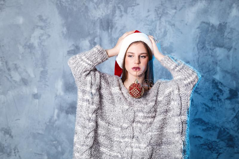 Merry Christmas and happy new year! Adorable girl with ball toy in mouth looks very puzzled. Close portrait on gray background. Girl in santa hat and sweater stock photos