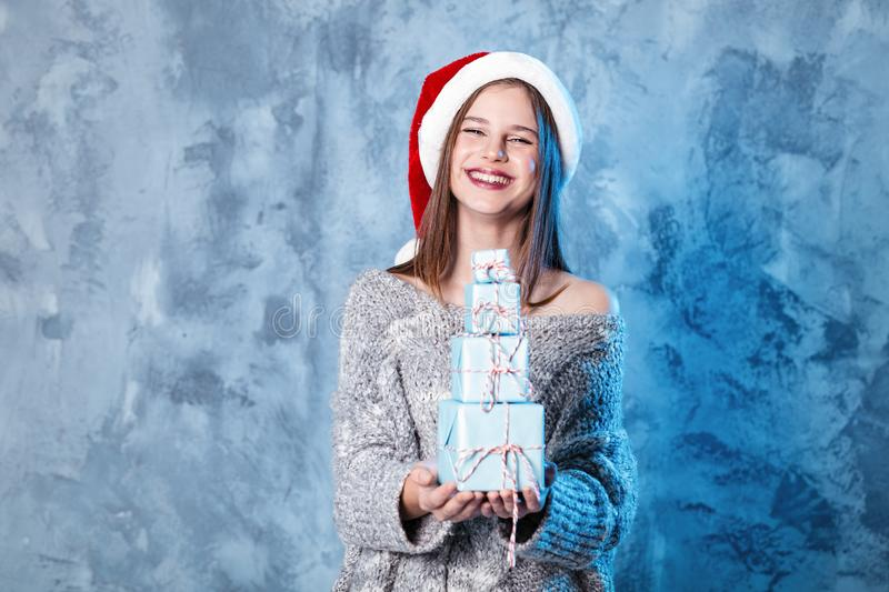 Merry Christmas and happy new year! Adorable happy girl hold many presents in hands. Close portrait on gray background. Girl in. Santa hat and sweater looks royalty free stock photo