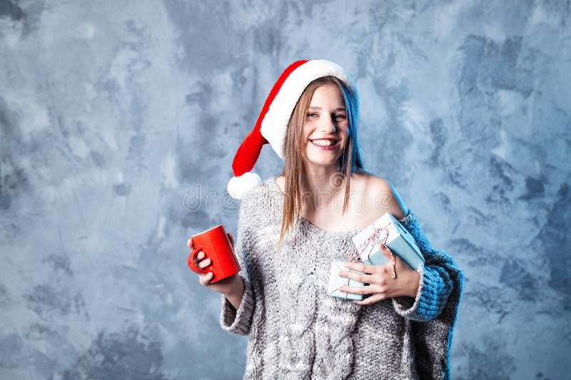 Merry Christmas and happy new year! Adorable happy girl with red cup and blue presents hold in hands. Close portrait on gray. Background. Girl in santa hat and royalty free stock images