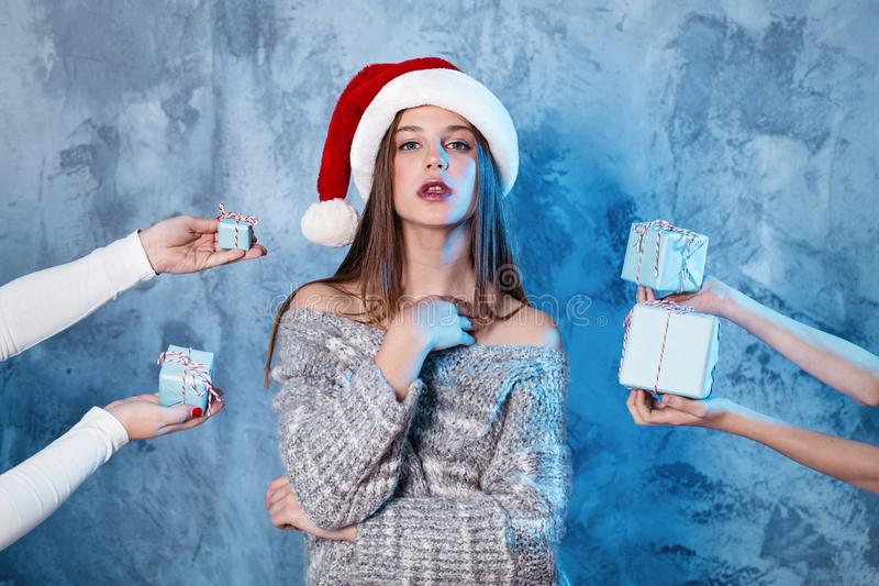 Merry Christmas and happy new year! Adorable happy girl stay between many presents in hands. Close portrait on gray background. Girl in santa hat and sweater stock photos