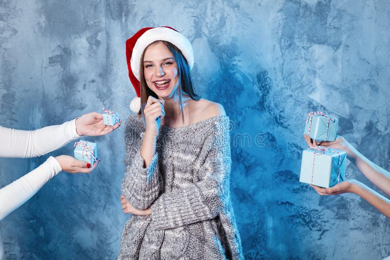 Merry Christmas and happy new year! Adorable happy girl stay between many presents in hands. Close portrait on gray background. Girl in santa hat and sweater stock images