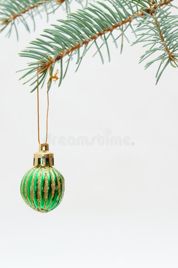 Merry christmas and a happy new year! The atmosphere of the winter holidays. Green spruce branch with decorations on a light background and free space for an royalty free stock images