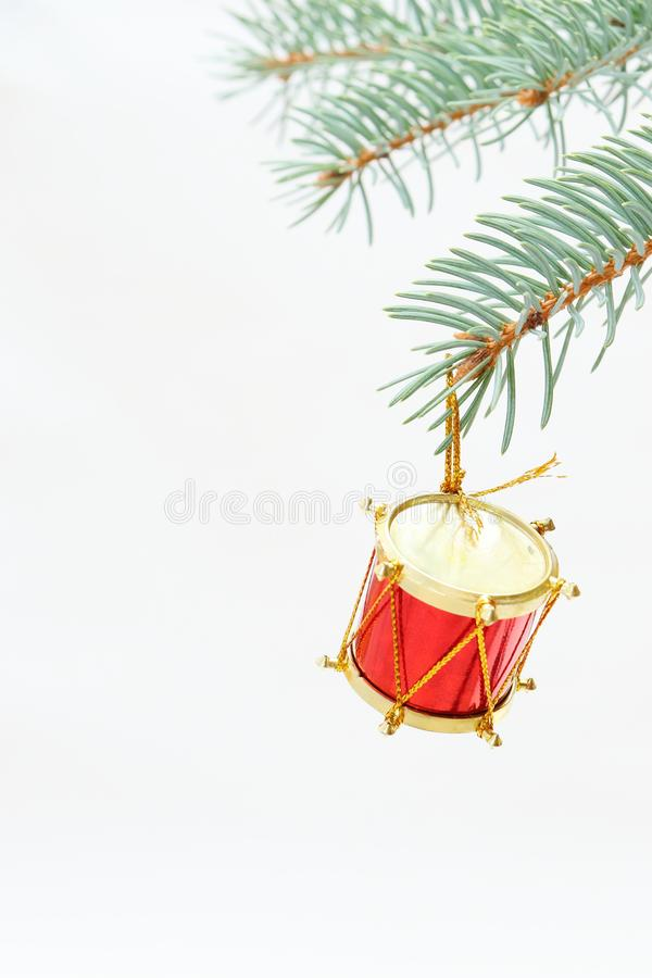 Merry christmas and a happy new year! The atmosphere of the winter holidays. Green spruce branch with decorations on a light background and free space for an royalty free stock photography