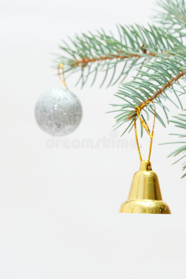 Merry christmas and a happy new year! The atmosphere of the winter holidays. Green spruce branch with decorations on a light background and free space for an stock photos