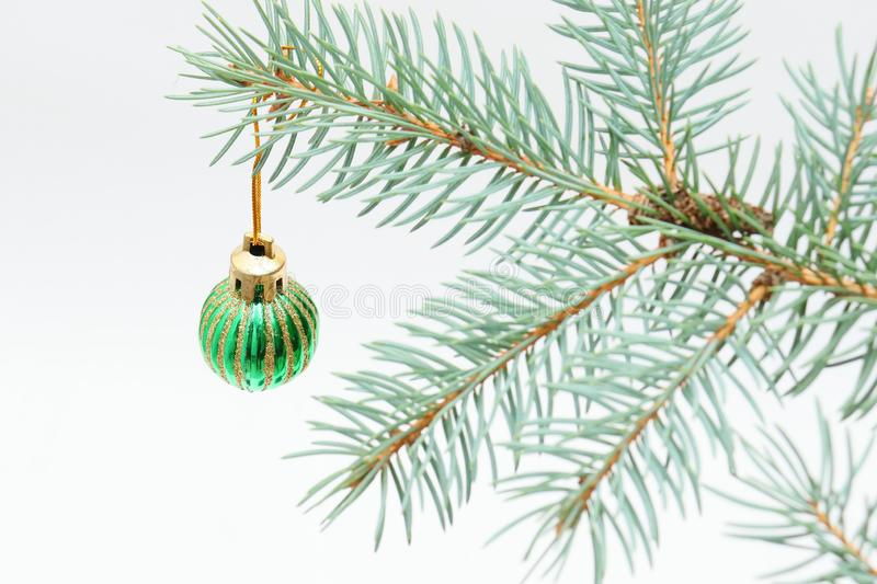 Merry christmas and a happy new year! The atmosphere of the winter holidays. Green spruce branch with decorations on a light background and free space for an stock photography