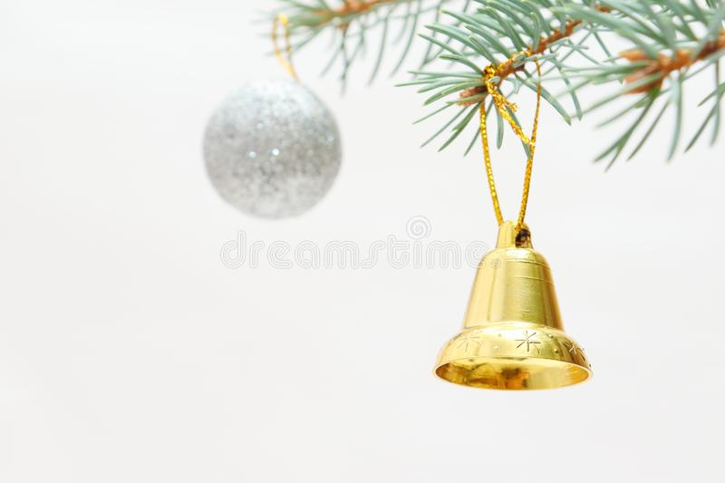 Merry christmas and a happy new year! The atmosphere of the winter holidays. Green spruce branch with decorations on a light background and free space for an royalty free stock image