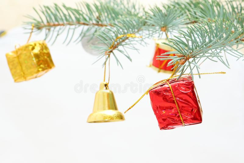 Merry christmas and a happy new year! The atmosphere of the winter holidays. Green spruce branch with decorations on a light background and free space for an royalty free stock photos