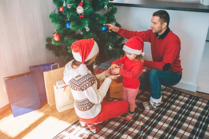 Merry Christmas and Happy New Year. Attractive picture of cute and nice family. They decorating Christmas tree. Young. Women holds toy with small girl. Man puts royalty free stock images