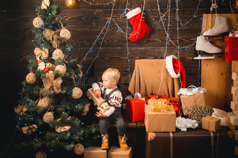 Merry Christmas and Happy New year. Babies. Portrait kid with gift on wooden background. Happy child with christmas gift. Box. Cheerful cute child opening a stock image